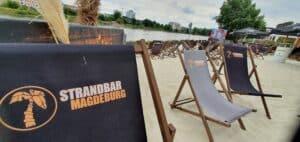 Liegestühle im Sand an der Elbe